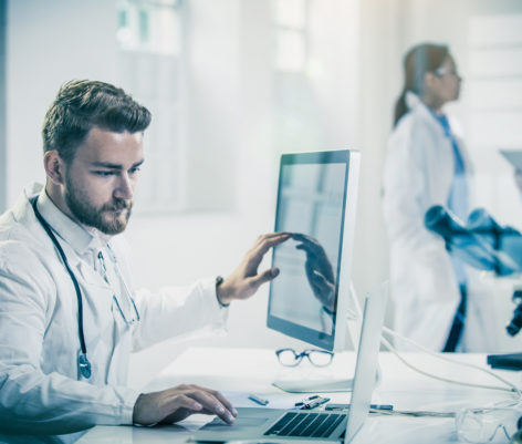 Male Doctor Using Computer With Colleagues Behind